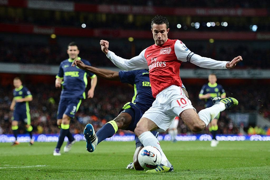 Robin van Persie of Arsenal is tackled by Emmerson Boyce of Wigan during the Barclays Premier League match between Arsenal and Wigan Athletic at Emirates Stadium on April 16, 2012 in London, England.