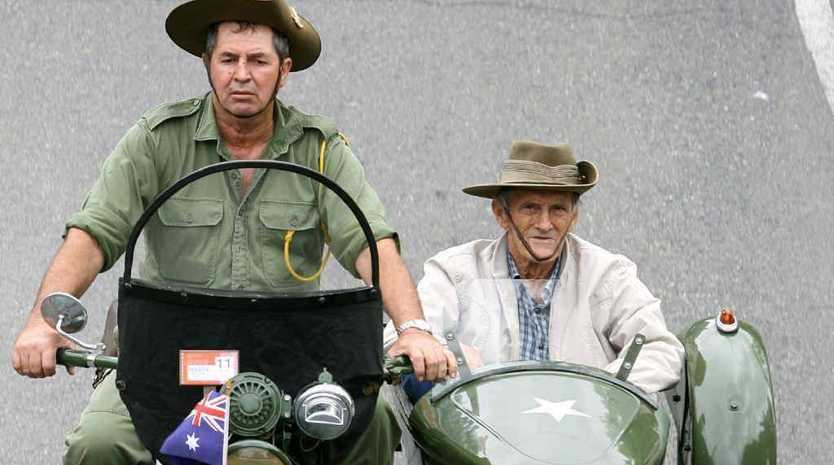 Andy Wright takes World War II digger Laurie Fraser for a ride during the Anzac Day parade on Quay St in Rockhampton yesterday.