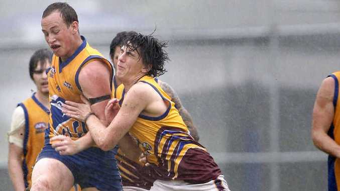 An Ipswich Eagles player struggles to get the ball away during Saturday's rain-affected Aussie rules match against Caboolture at Limestone Park.