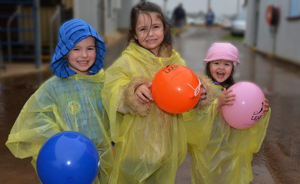 PREPARED FOR THE WEATHER: Snug as a bug in the rain are Summa Collins, Tyson and Nikita Saunders at the Blackbutt Show. Photo: contributed