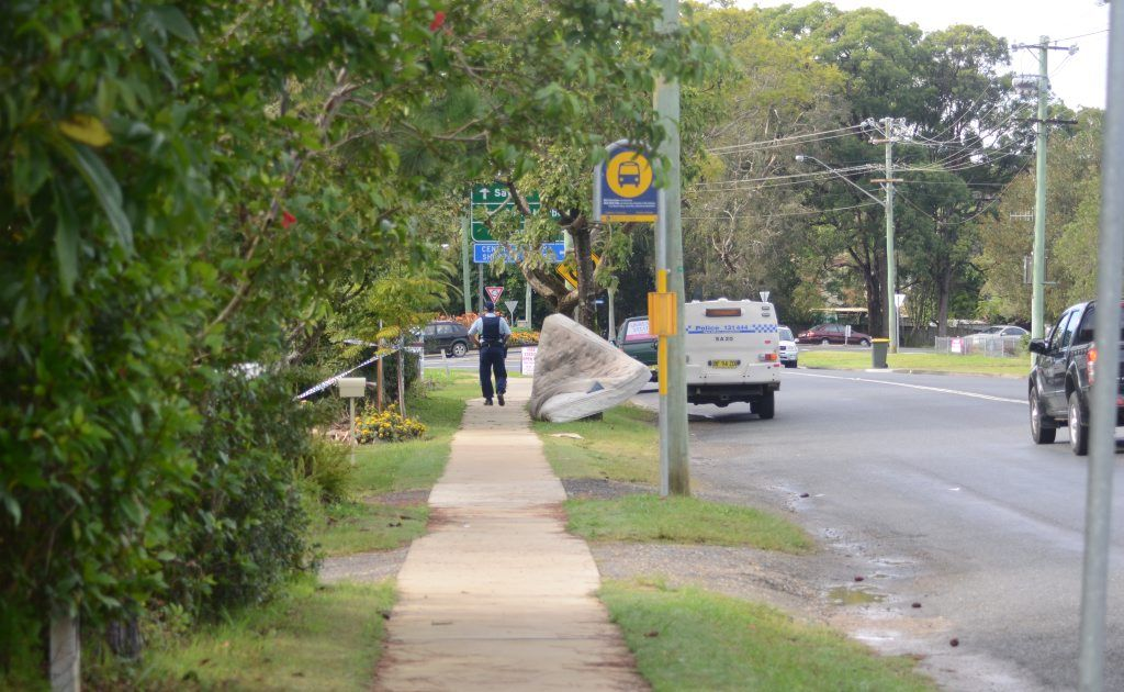 Police keep the public away from the Toormina residence of a woman allegedly murdered yesterday.