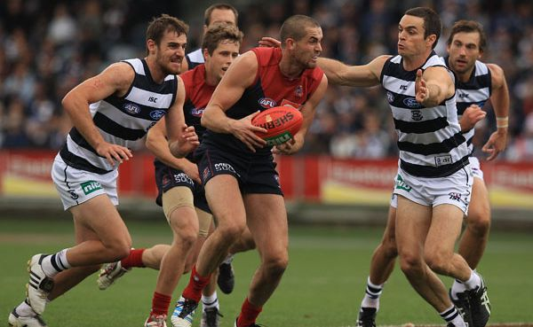 James Sellar of the Demons collects the ball under pressure from Matthew Scarlett (R) of the Cats during the round six AFL match between the Geelong Cats and the Melbourne Demons at Simonds Stadium.