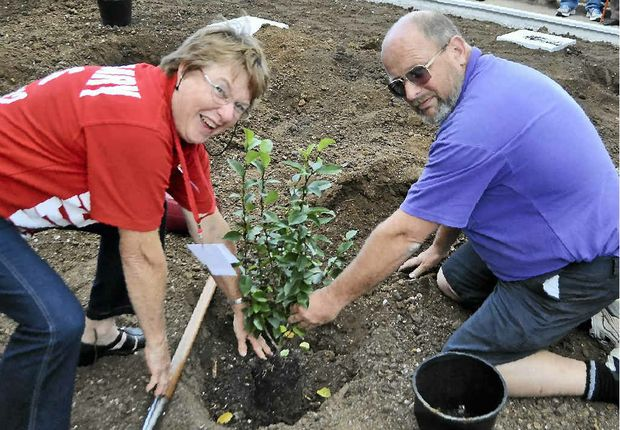 Margaret Bryant and Greg Marsh plant a tree outside the front of the school.