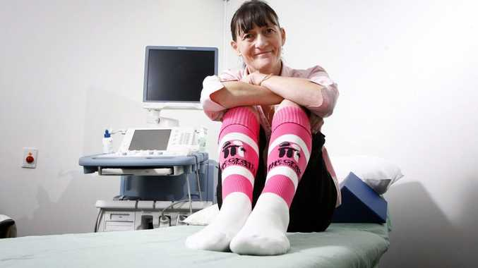 Breast cancer nurse Karen Miles sits on an exanimation bed and shows off her McGrath Foundation football socks. The McGrath Foundation is launching a Pull On Your Socks campaign for football clubs to raise raise money for breast cancer. Photo: Claudia Baxter / The Queensland Times