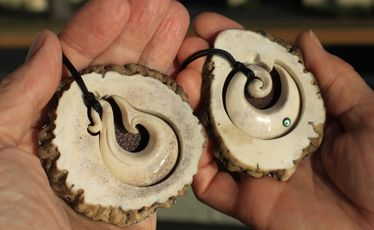 Fishhook and koru bone carvings produced by Jim and Chris Eagles at Pacific Carvers.