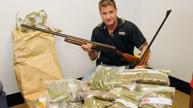 Plain clothes Senior Constable Craig Kable shows some of the drugs and guns.