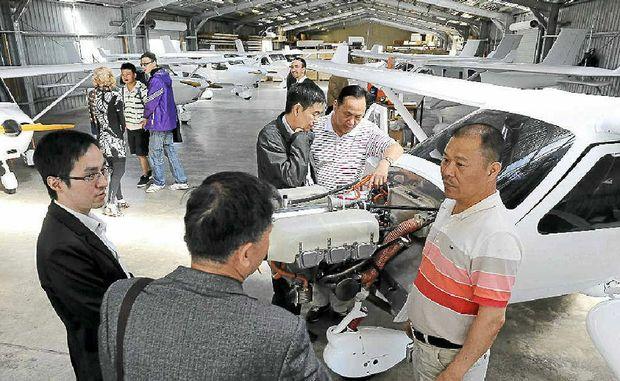 Nanning delegates Jian Jun Chen and Ning Teng study the engine of a Jabiru during their visit.