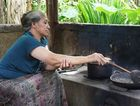 A woman roasts beans to make kopi luwak, after they've been conveniently processed by the Asian palm civet.