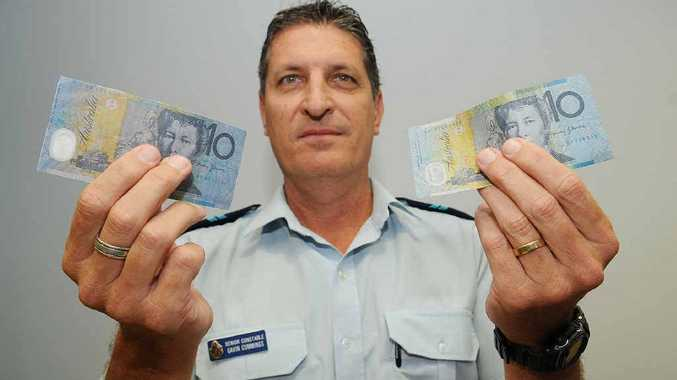 Senior Constable Gavin Cummings shows off the fake note (left) and the real $10 note (right).