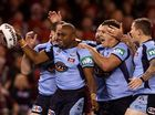 The NSW Blues players celebrate after scoring the opening try in State of Origin I.