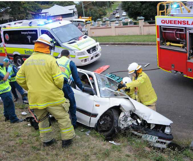 Firefighters and ambulance officers work to free Grace Harold after she crashed her car into a rock retaining wall on Tuesday afternoon.