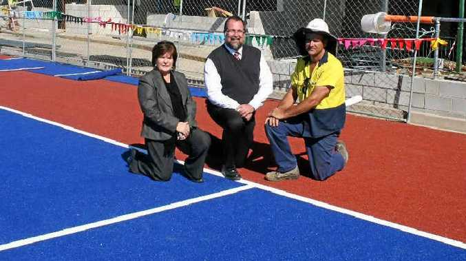 Warwick hockey rebuilding committee members Sheryl Windle (left) and Glenn Eastwell (right) with Mayor Peter Blundell in front of the new dugouts at Queens Park.