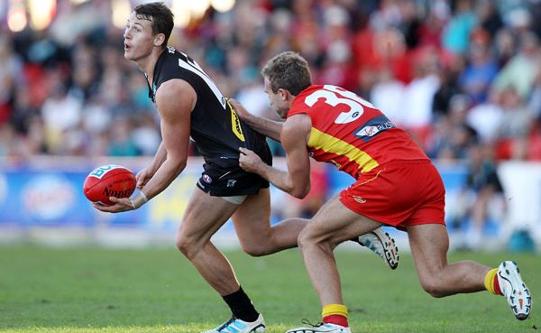 Ben Jacobs of the Power is tackled by Sam Iles of the Suns during the round nine AFL match between the Gold Coast Suns and Port Adelaide Power at Metricon Stadium.