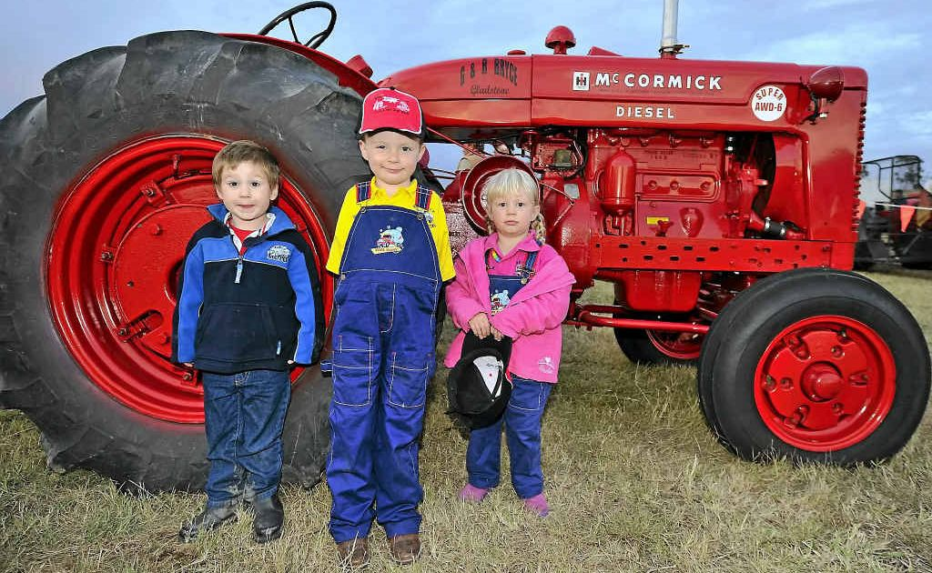 Josh Zumbansen, 3, Henry Bryce, 4, and sister Annabelle, 2, stand in front of a beautifully restored McCormick Diesel tractor at the heritage machinery and aircraft show.