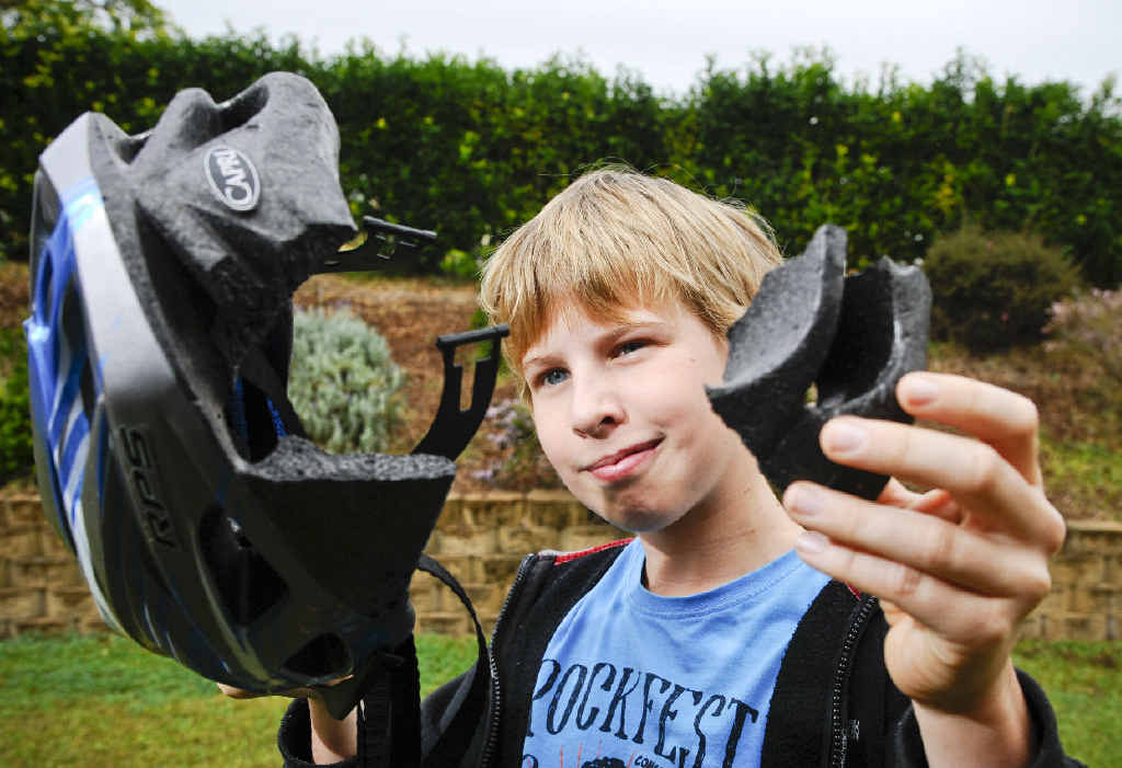 Braden Cooper, 12, shows off the large chunk taken out of his helmet after he had a bike accident last year.