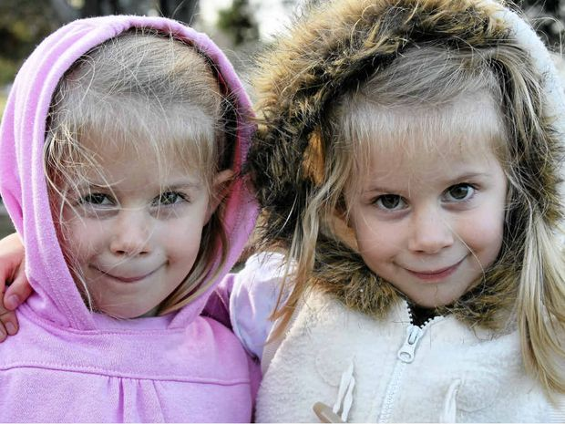 Twins Hannah and Abby Moody stay rugged up while playing in the park.