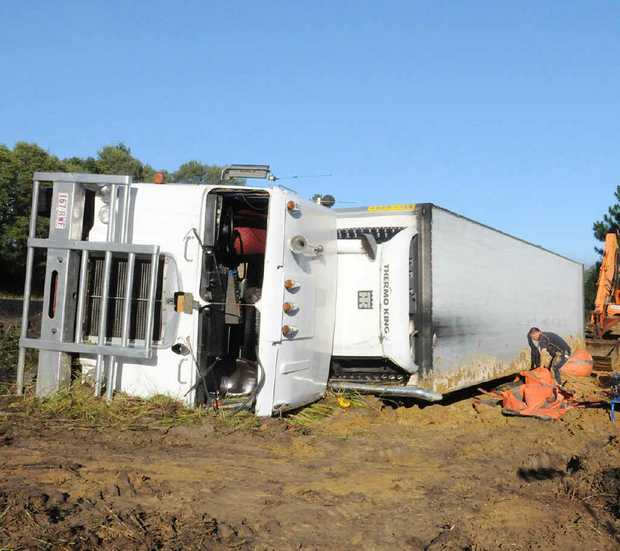 This refrigerated truck ended up on its side after the driver lost control on the Bruce Hwy.