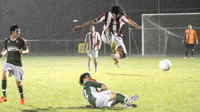 Lion's Daniel Allen hurdles a Strikers player as he slides in for a tackle in the rain Saturday night.