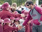 Maroons five-eighth Johnathan Thurston meets Roma school children during the street parade.