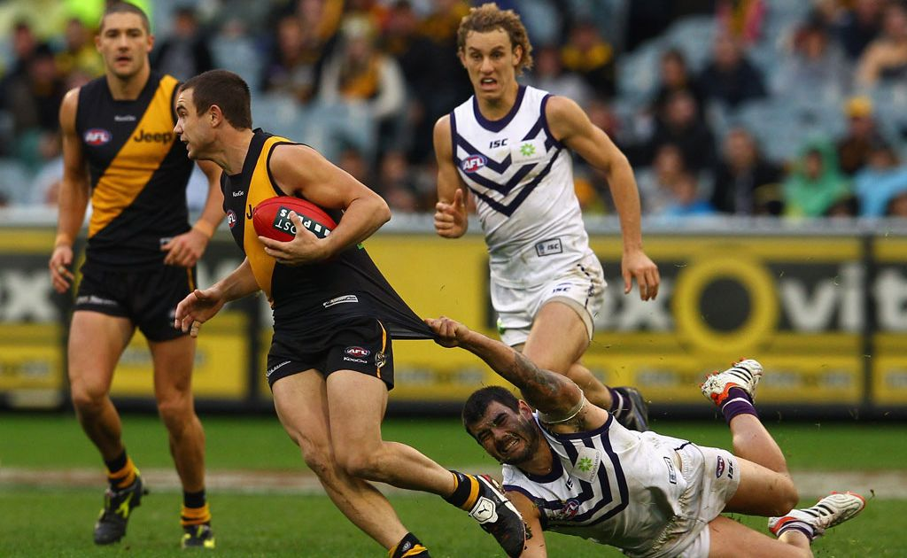 Addam Maric of the Tigers is challenegd by his opponent during the round 11 AFL match between the Richmond Tigers and the Fremantle Dockers at Melbourne Cricket Ground