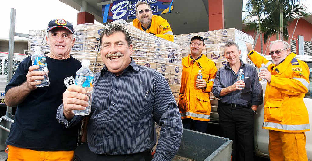 Brothers Leagues Club general manager Mark Hennelly presents another two pallets of bottled water to local rural fire brigades while senior Ripley Rural Fire Brigade fire fighter Brian Evans (left) looks on.