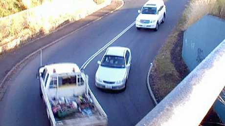 The driver of a white utility narrowly misses hitting an oncoming car after crossing double white lines.