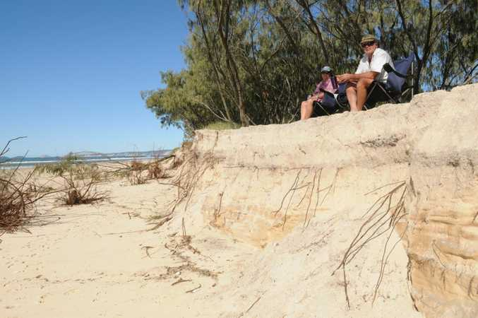 Doreen and Melton Erickson from Yandina Creek sit at the top of an eroded sand dune at Inskip Point on Monday.