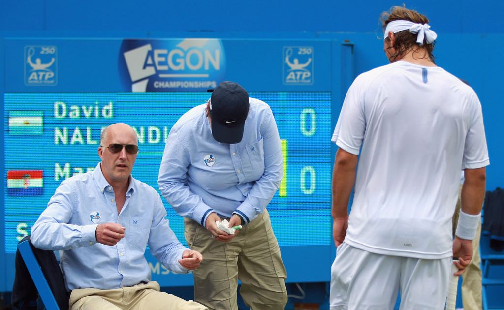 David Nalbandian looks on as a linesman is treated for a leg wound after he lashed out during the final of the Queens Club tennis tournament.