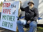 Protester Robert Ghysen with his sign yesterday outside the Surat basin Energy and Mining Expo.