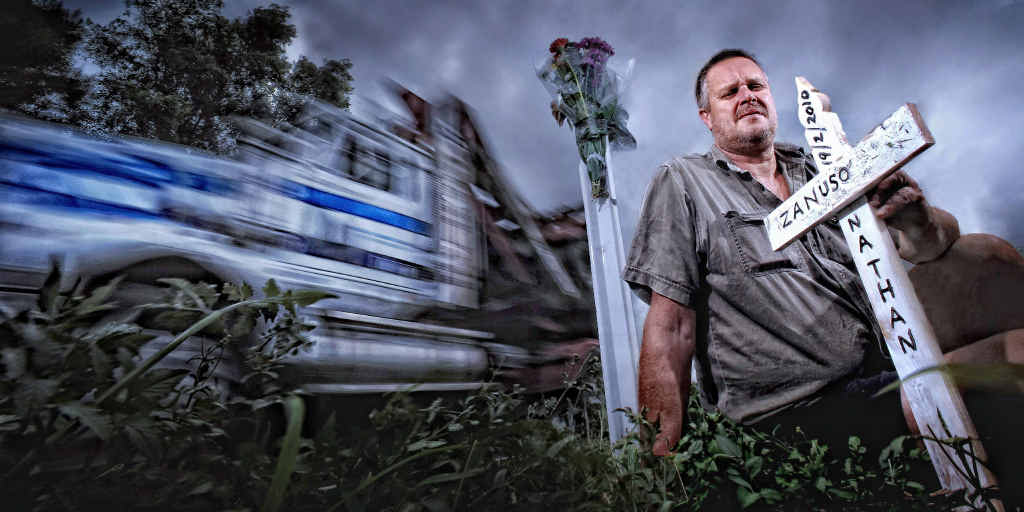 Paul Zanuso, father of Nathan Zanuso who was killed on the Pacific Highway in 2010, plants a cross at the scene.