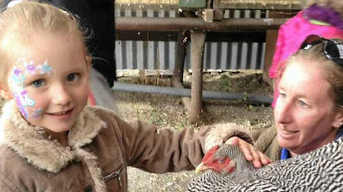 Brianna Ward, 5, pats a chook held by Kylie Nixon.