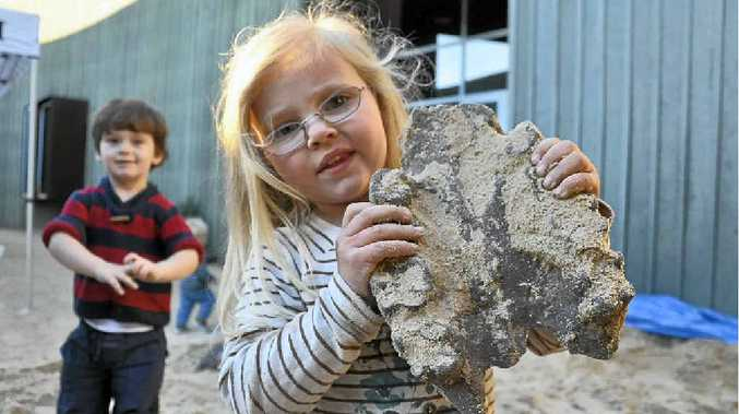 Briar Parker shows off a fossil she found with the help of friend Raymond Kear.