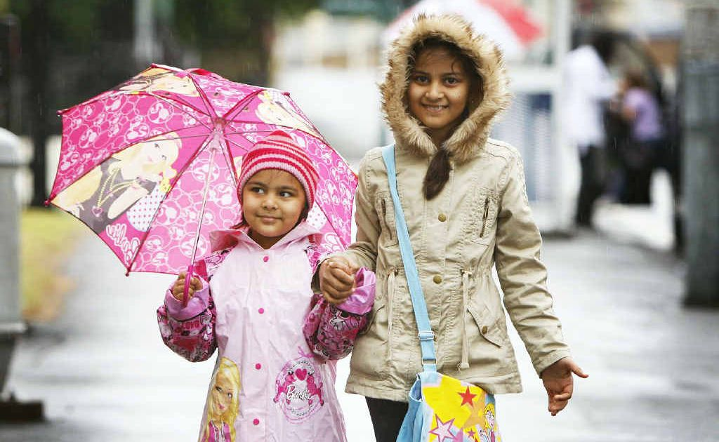 Sharia Adnan, 3, and Shanefa Adnan, 8, of Booval, brave the wet weather for a trip into the city. Photo: David Nielsen