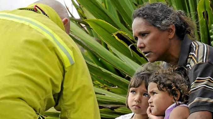 Senior firefighter Monty Clelland checks on Deborah Fuller and her daughters Ciara and Rihanna Whittaker at a crash scene. Paramedics, firefighters and rescue volunteers have been named Australia's most trustworthy professions.