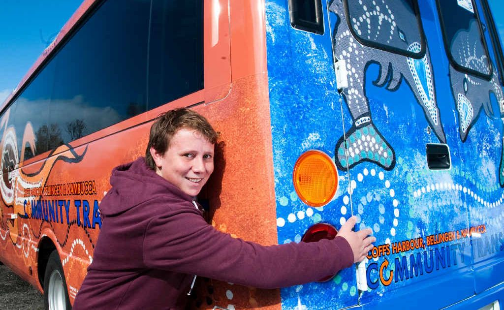 Artist Trai Dungay embraces the Community Transport bus that bears his art work.