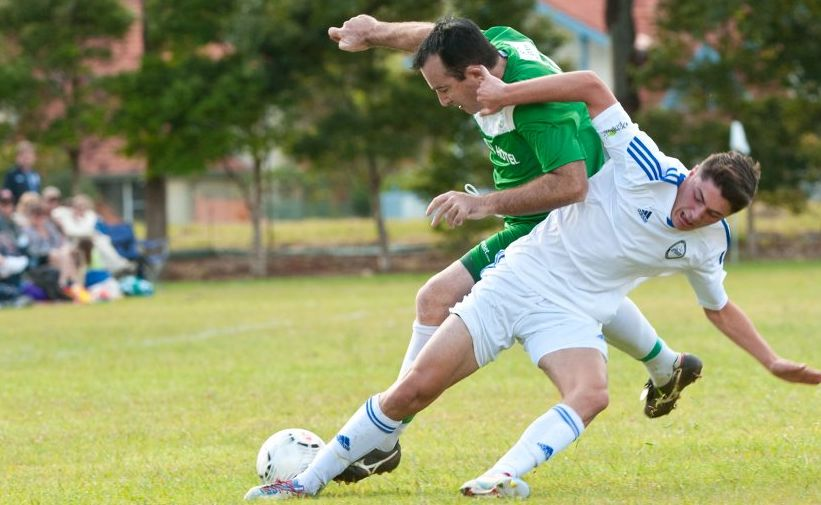 Sawtell captain Grant Martin is tackled in full flight by a Northern Storm defender.
