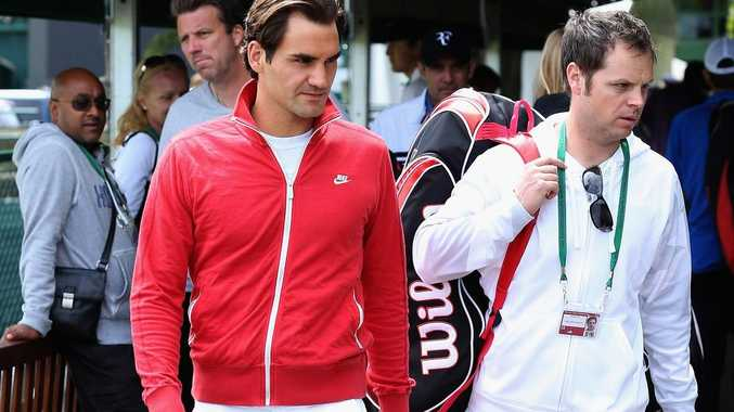 Roger Federer (L) arrives for a practice session at Wimbledon on July 1 in London, England.