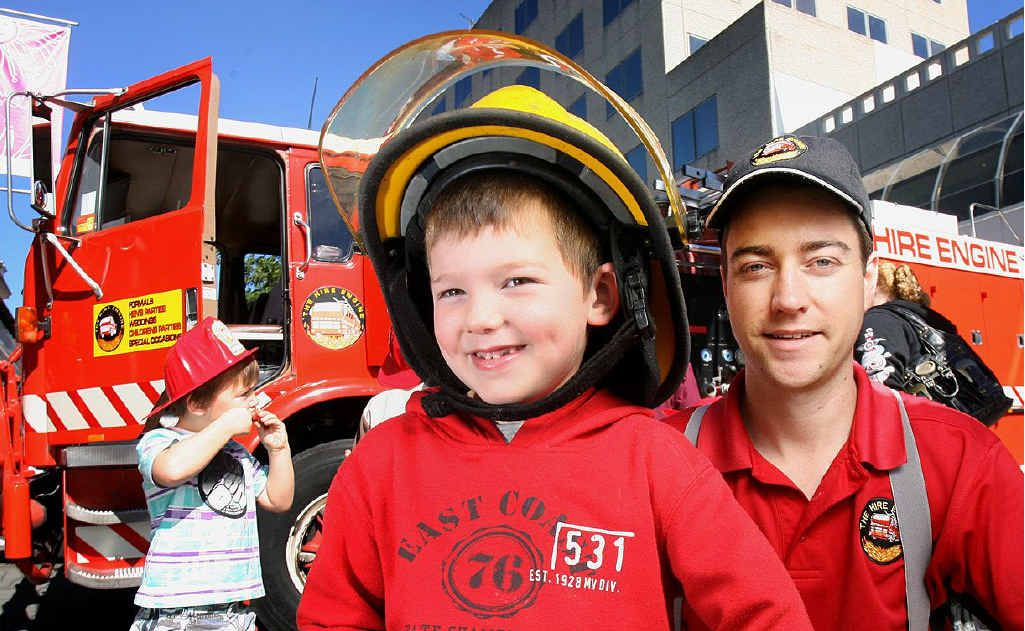Ryan Shaxson feels what it is like to be a fireman with Brad Threlkeld from The Hire Engine in the Ipswich Mall on Wednesday.