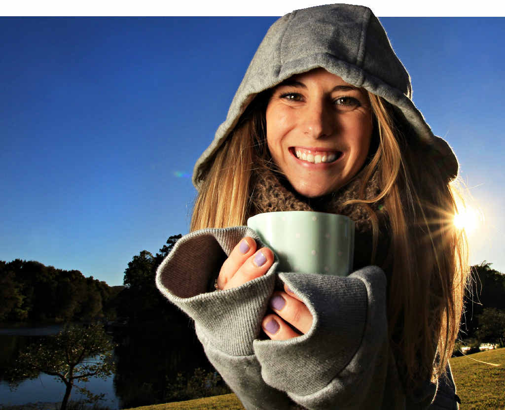 Lauren Grounsell, 20, rugs up in a hoodie and has a cup of hot chocolate during yesterday's clear winter weather.