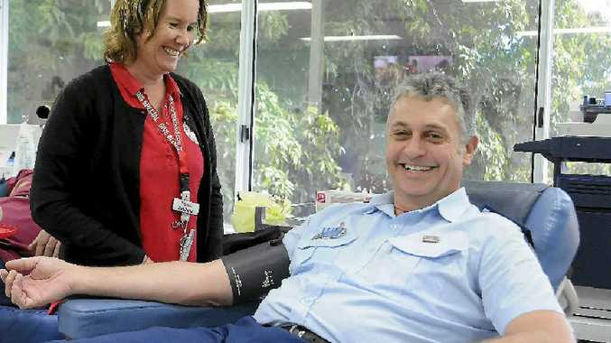 Inspector Les Bulluss donates blood with Red Cross staff member Stephanie Cairns.