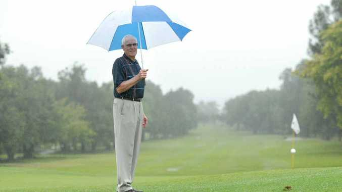 Eric Duck stands in the rain on the 18th green at the Mackay golf course after the first day of the Mackay Open was called off yesterday. Today's round has also been called off.