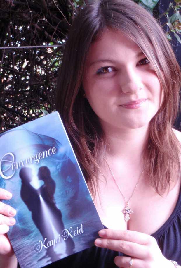 Kayci Reid with her published novel, Convergence.