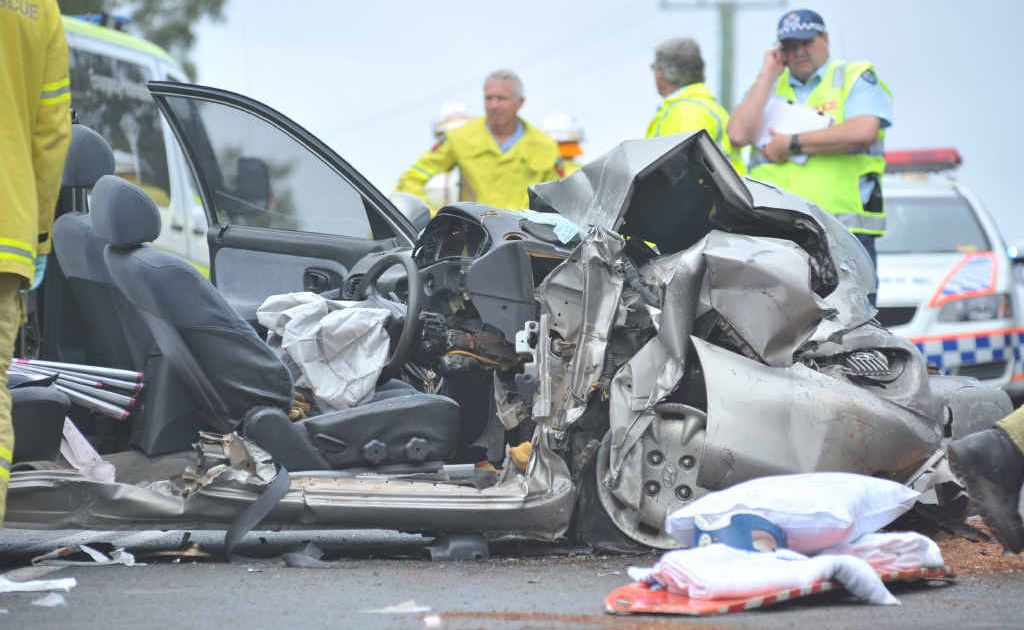 Paramedics and emergency crews work on the female driver of a car involved in a head-on crash on Thursday.