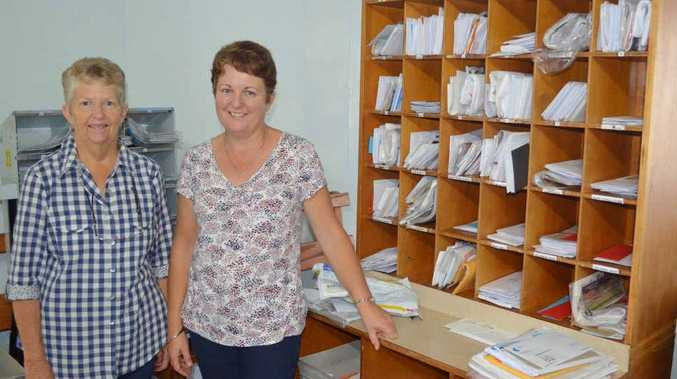 Val Vesey and Bev Richardson work hard to fill the post office boxes with mail for Bluff residents.