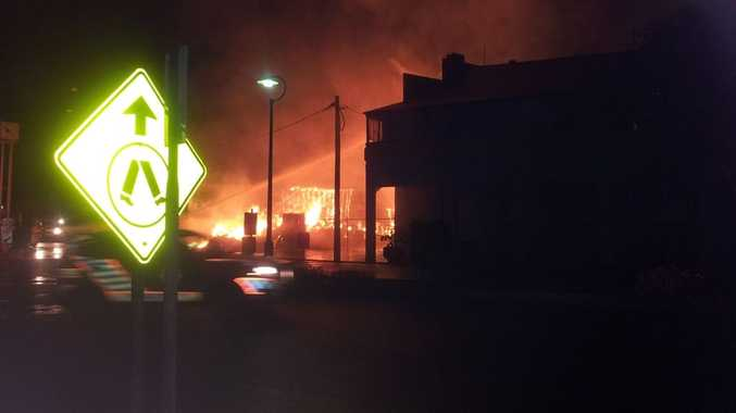 Fire engulfs a Millmerran business last night as firefighters try to stop it from spreading to the Rams Head Hotel.