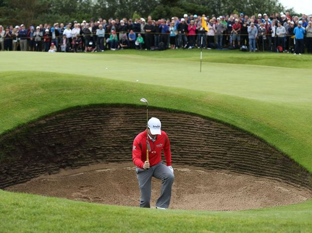 Rory McIlroy of Northern Ireland reacts to his bunker shot on the sixth hole during the second round of the 141st Open Championship at Royal Lytham & St Annes Golf Club.