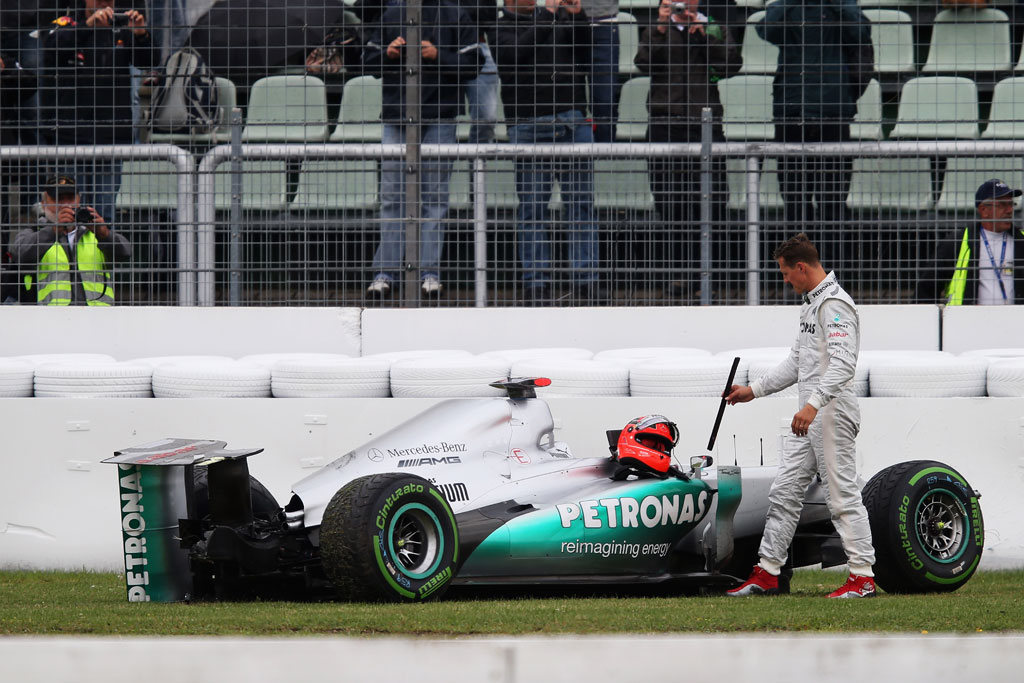 Michael Schumacher of Germany and Mercedes GP stands with his car after he span and crashed out during practice for the German Grand Prix at Hockenheimring