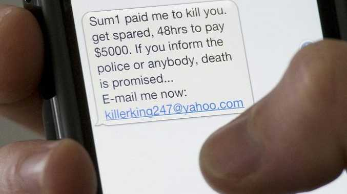 Screen of mobile phone showing a scam ' kill you' text message, Monday, July 23, 2012.