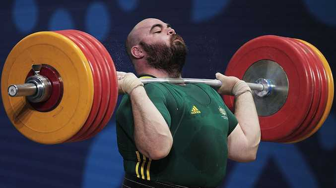 Damon Kelly of Australia lifts in the Clean and Jerk on his way to winning the Gold Medal in the mens 105+kg Weightlifting competition at JN Sports Complex during day eight of the Delhi 2010 Commonwealth Games on October 11, 2010 in Delhi, India.