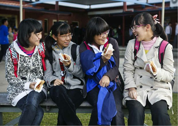 SNAG TIME: Beijing school students Stephanie Ji, Will Liang, Gabriel Zhang and Sterope Cheng enjoy a sausage sandwich on a visit to Clarence Valley Anglican School. Photo: Adam Hourigan